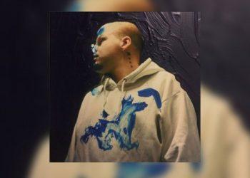 Man with blue paint deisgn on sweatshirt