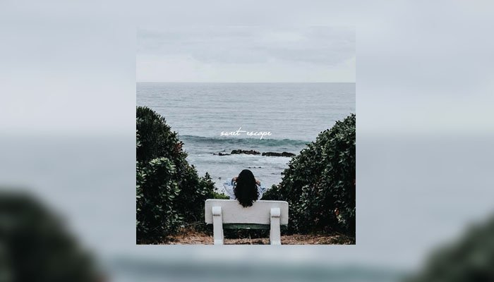 Girl on bench looking at sea light blue colour
