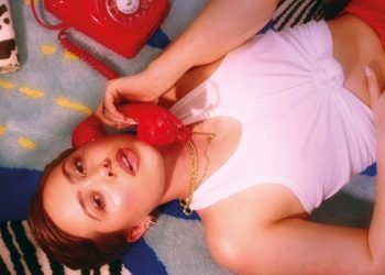 Girl on floor with red telephone