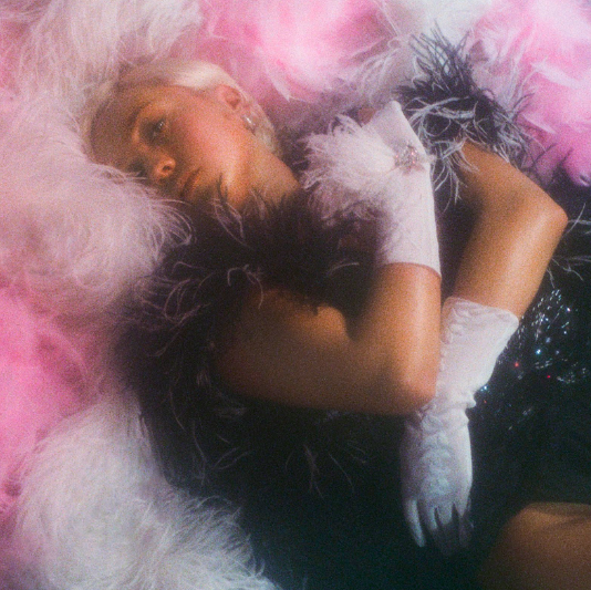 Blonde girl in pink feathers lace gloves