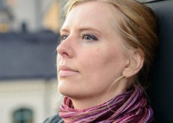 Blonde Swedish woman against a wall with scarf