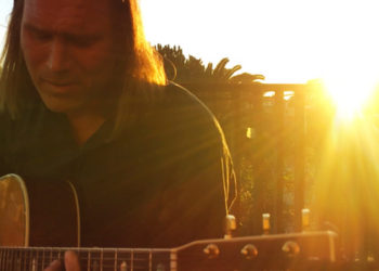 man with guitar sunshine haze