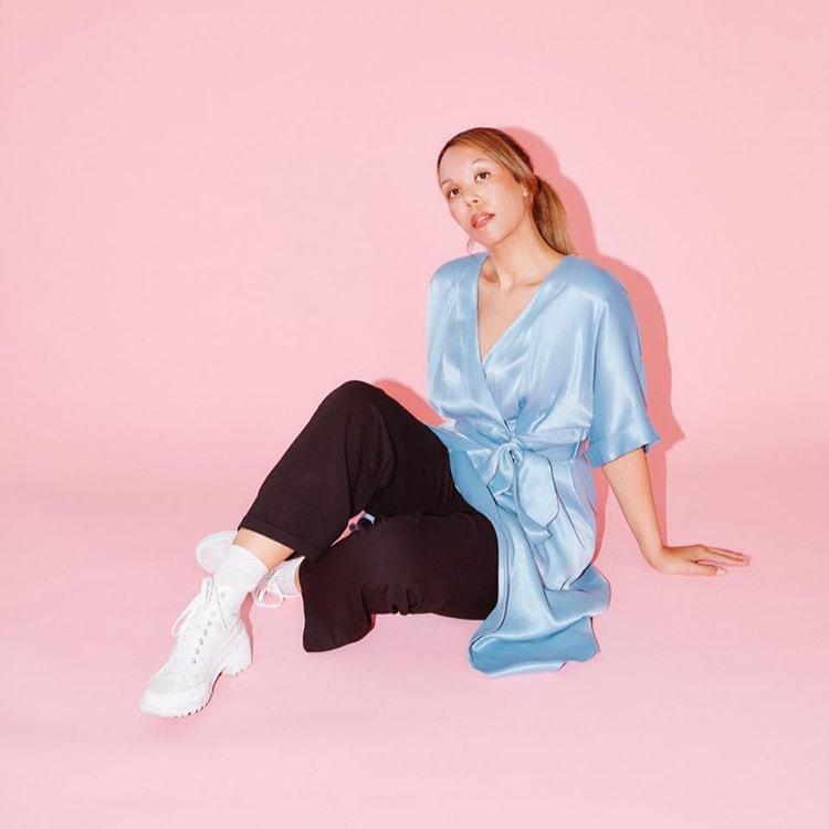 Pick backround girl in blue silk top