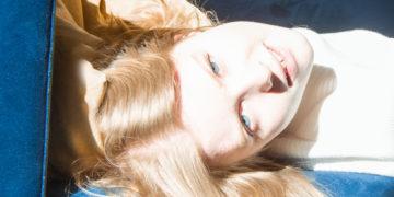 Blonde girl on sofa angle