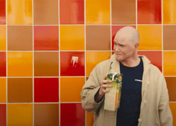 Man in front of colourful tiled wall