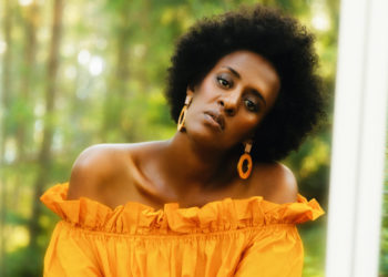 Black woman with afro and orange top
