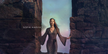 WOman stand between stone walls