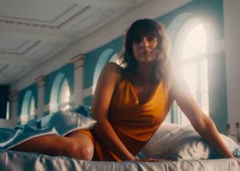 Woman in orange top on a mattress