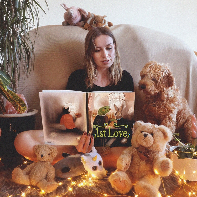 Girl reading book to soft toys